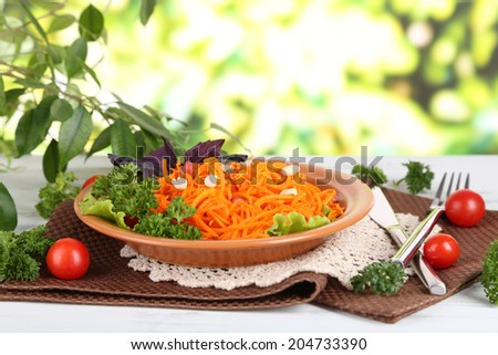 Carrot salad on plate on napkin on wooden table on nature background