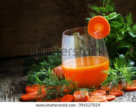 Carrot smoothie in a large glass decorated with a slice of carrot, green leaves, old wooden background, selective focus - stock photo