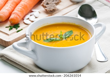 Carrot soup in white bowl topped with fresh mint
