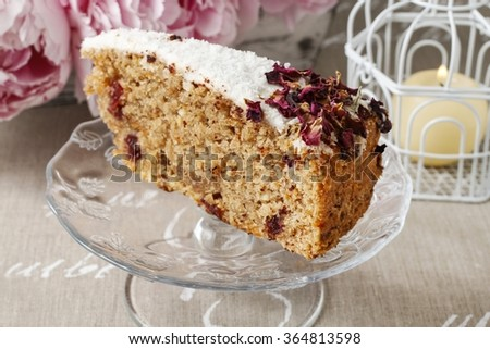 Carrot vegan cake with coconut icing and dried wild rose petals (rosa rugosa)