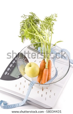 Carrots and apple surrounded by a measuring tape on a white bathroom scale. Blank display. - stock photo