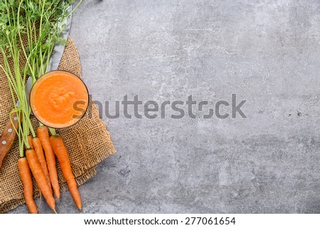 Carrots and carrots juice on stone background - stock photo