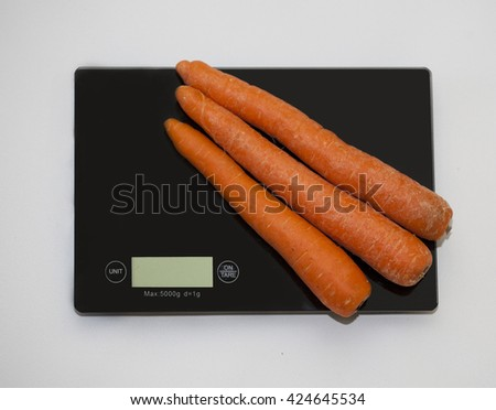 Carrots on a digital white kitchen scale. (weighing products) - stock photo