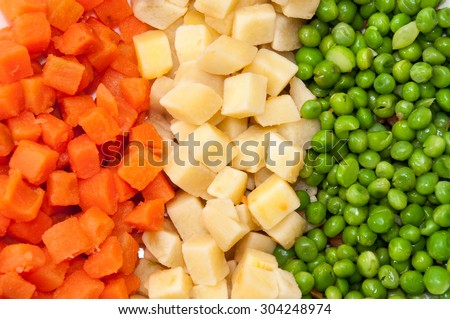 Carrots, potatoes and peas prepared for the Russian salad. - stock photo