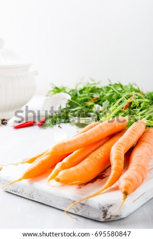 Carrots with vegetarian cooking ingredients. Bio healthy food concept. Organic vegetables on old wooden cutting board. Copy space.
