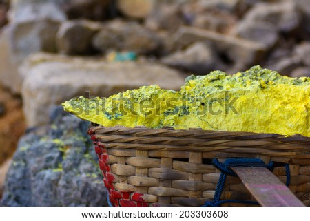 Carrying basket sulfur, volcano in Indonesia - stock photo