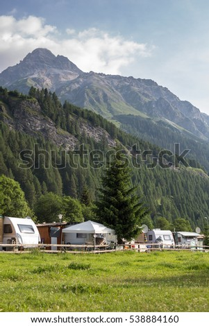 Cars and campervans in an outdoor mountain camping site staying here overnight