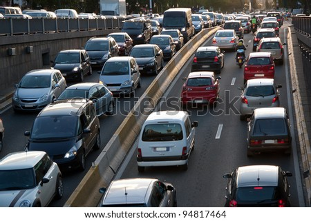 Cars and motorcycles going along the four lane highway. - stock photo