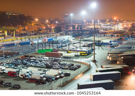 Cars and trucks on a large parking space at Barcelona industrial port at night. Spain