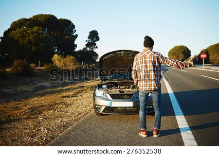 Cars - driver trying stop car in travel because his car broken. Young man stand on freeway and shows thumbs up. Young interracial man in their twenties, Caucasian man.  - stock photo