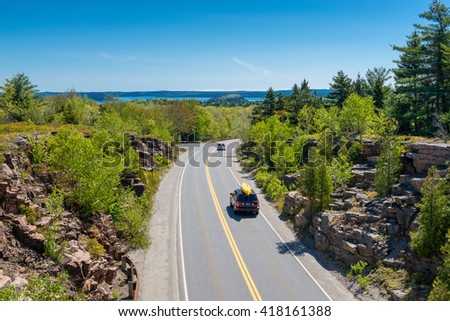 Cars driving on road in Acadia National Park, Maine, USA. One car carries a canoe on its roof. - stock photo