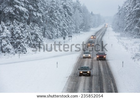Cars driving on snow road - stock photo