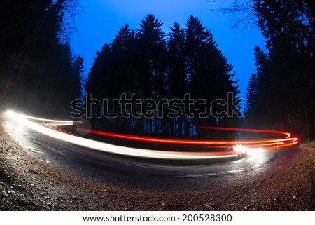 Cars going fast through a curve on a forest road at dusk, on a rainy day - i.e. Potentially dangerous driving conditions - stock photo