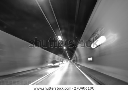 Cars in a tunnel - Snow shutter speed abstract car tunnel effect showing motion and speed - black and white - stock photo