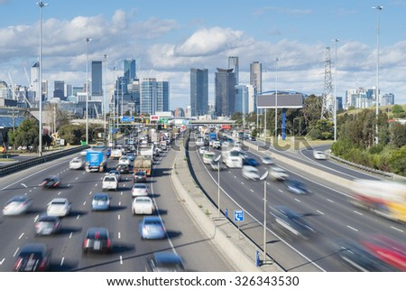 Cars in motion blur in highway with skyscrapers in the background during daytime - stock photo