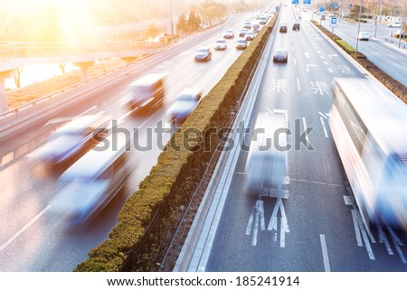 Cars in motion blur on street during sunset - stock photo