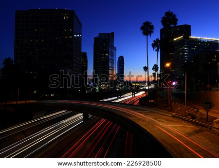 Cars leaving light trails on a downtown Los Angeles freeway at dusk. - stock photo