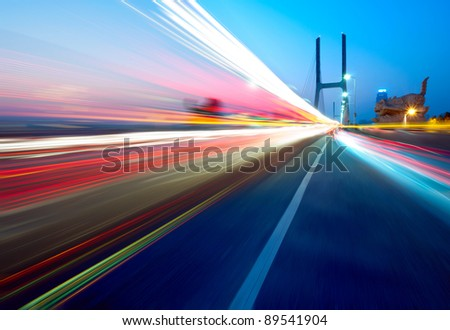 cars light trails on the modern bridge at dusk - stock photo