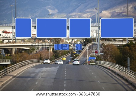 Cars on highway with blank directional road signs - stock photo