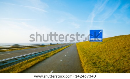 Cars on the highway and an exit sign - a transportation/traffic concept image. A bicycle path is also visible on the image. - stock photo