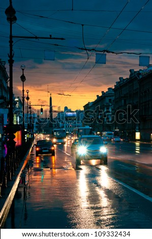 Cars on wet road at night in the center of the city - stock photo