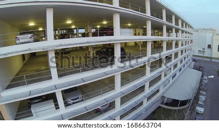 Cars parked in multistoried parking at evening. View from unmanned quadrocopter - stock photo