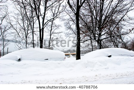 Cars parked on a street covered in snow during the winter season storm blizzard - stock photo
