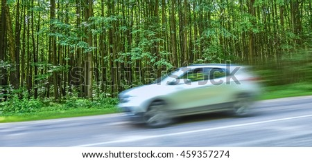cars traveling at high speed on the road against  background of  forest