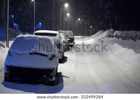 Cars under snow at night time - stock photo