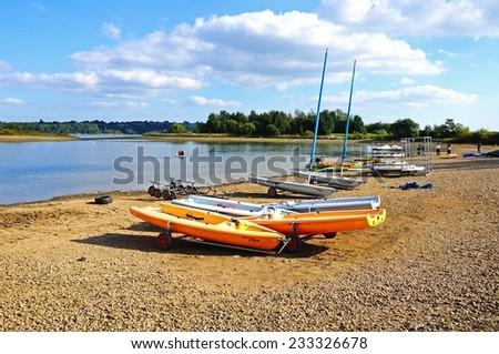 CARSINGTON, UK - SEPTEMBER 7, 2014 - View across Carsington Reservoir with small boats on the shoreline, Carsington, Derbyshire, England, UK, Western Europe, September 7, 2014. - stock photo
