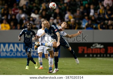 CARSON, CA - APRIL 12: Los Angeles Galaxy defender Omar Gonzalez #4 & Vancouver Whitecaps M Kenny Miller #9 during the MLS game between the Los Angeles Galaxy & the Vancouver Whitecaps April 12 2014 - stock photo