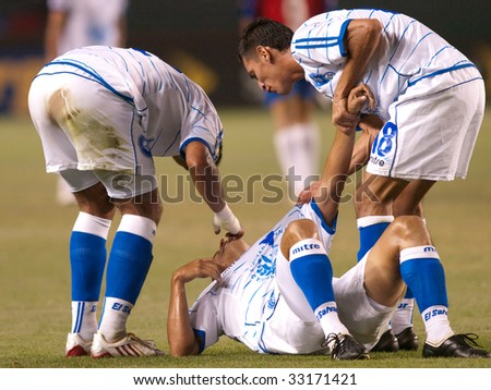 CARSON, CA. - JULY 3: Concacaf Gold Cup soccer match, Costa Rica vs. El Salvador at the Home Depot Center in Carson. Injuried player with team mates helping him up. July 3, 2009. - stock photo