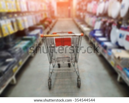 Cart in supermarket aisle motion blur background - stock photo