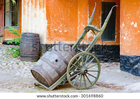 Cart with a wooden cask or barrel outside a building. Another cask stands in the background. Walls on building are orange. Place has a vintage feel to it. Open hole in cask. - stock photo