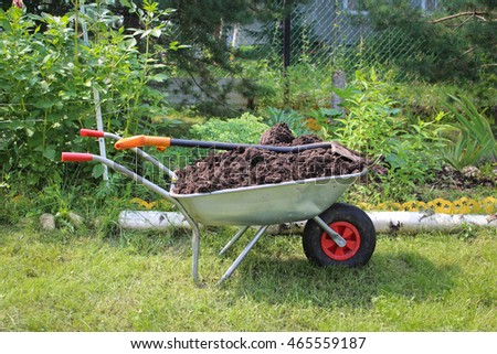 Cart with ground and shovel in the garden