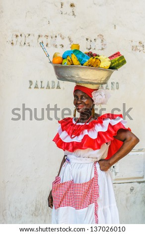 CARTAGENA, COLOMBIA - DEC, 02: Palenquera woman sells fruits at Plaza Santo Domingo on December, 02, 2009 in Cartagena, Colombia - stock photo
