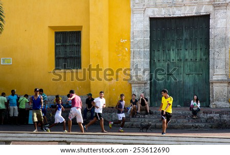 Cartagena, Colombia - February 23, 2014 - Children and teens play soccer in square in front of a church as parents and tourists what in the colorful streets of Cartagena's Getsemani neighborhood. - stock photo
