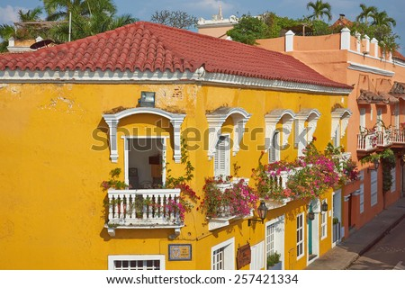 CARTAGENA, COLOMBIA - JANUARY 24, 2015: Bright yellow facade covered in plants and flowers in the historic UNESCO World Heritage Site of Cartagena de Indias in Colombia - stock photo