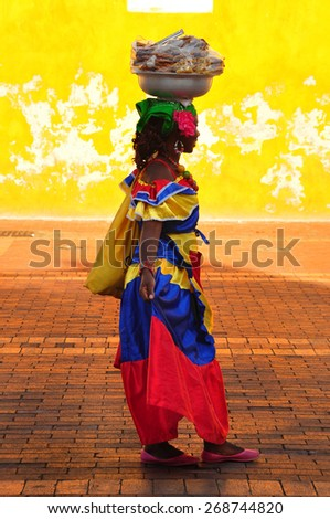 CARTAGENA DE INDIAS, COLOMBIA - JUNE 15, 2014: Colombian woman in Cartagena de Indias with the traditional dress. In Colombia is usual to transport fresh fruit and food on the head. - stock photo