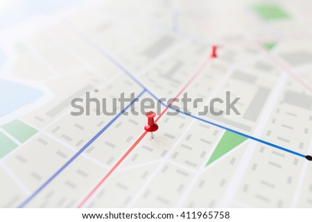 cartography, location and navigation concept - close up of map or city plan with pin - stock photo