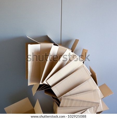 carton open boxes stacked on curved circle shape on gray wall - stock photo
