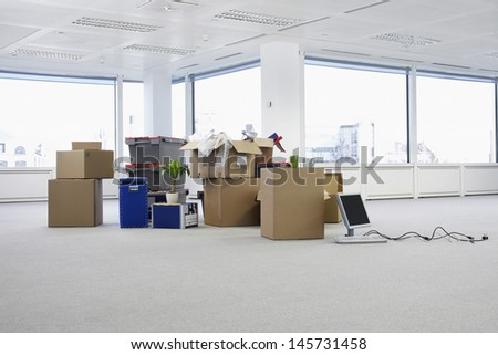 Cartons and equipment on floor of empty office space - stock photo