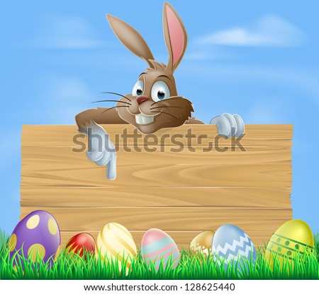 Cartoon Easter bunny pointing at blank wooden sign with painted chocolate Easter eggs in green field