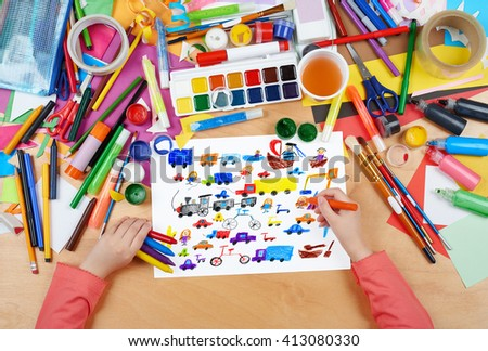 cartoon game toy and people collection child drawing , top view hands with pencil painting picture on paper, artwork workplace - stock photo