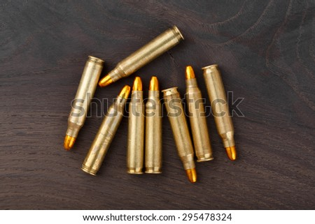 Cartridges on old wooden table. - stock photo