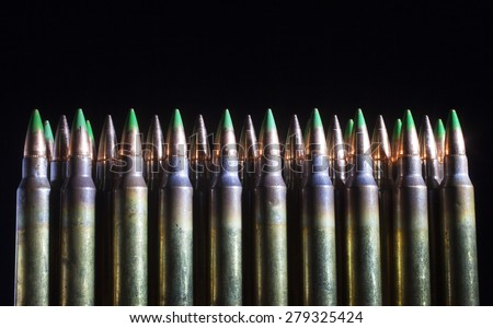 Cartridges with green tipped bullets on front of others with steel