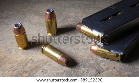 Cartridges with hollow point bullets and magazines for a semi automatic handgun - stock photo