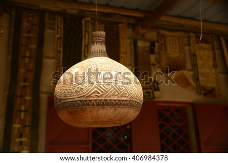 Carved decorative African gourd drinking vessel hanging on post - stock photo