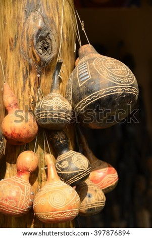 Carved decorative African gourds hanging on post - stock photo