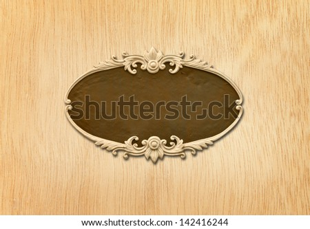 carved oval wood frame on wood background - stock photo
